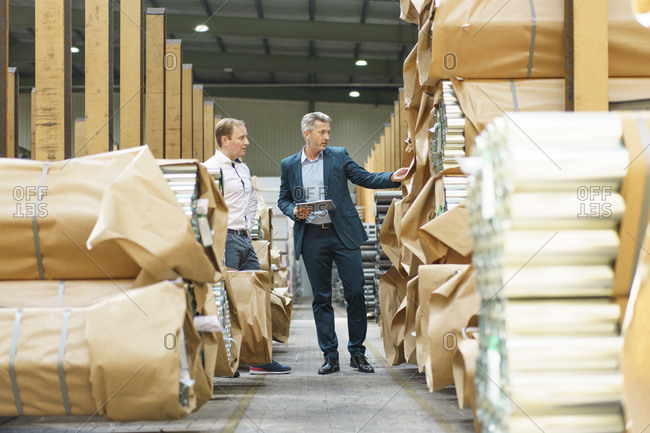 Two businessmen in a factory storehouse with steel pipes
