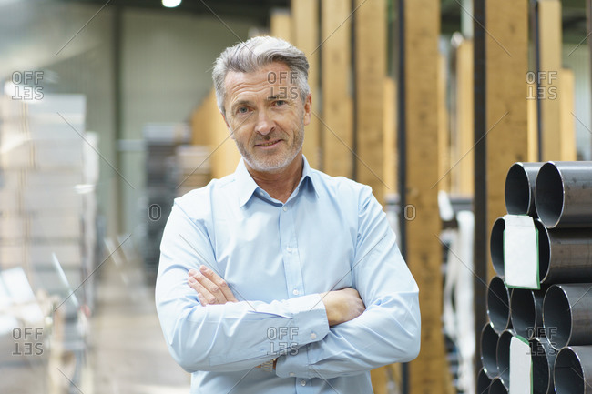 Portrait of a confident mature businessman in a factory storehouse with steel pipes