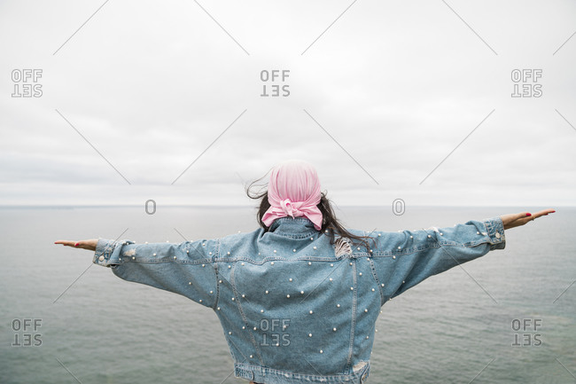 Young female cancer survivor with arms outstretched looking at sea against cloudy sky