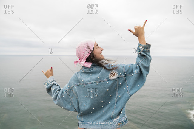 Female cancer survivor smiling and dancing against sea