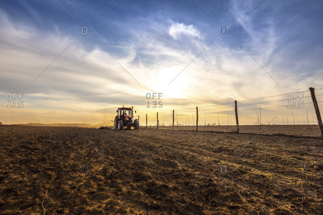 Farmer in tractor plowing agricultural land against cloudy sky