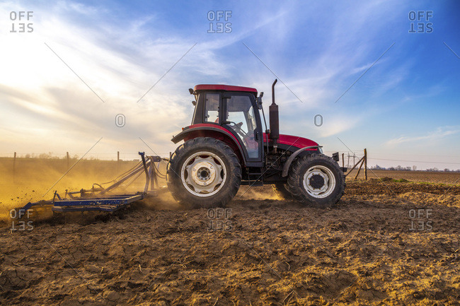 Man in tractor plowing agricultural field against cloudy sky