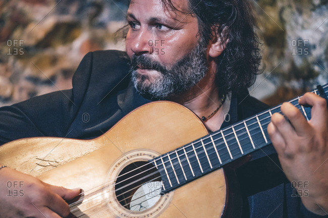 Close-up of bearded mature man playing flamenco on guitar in nightclub