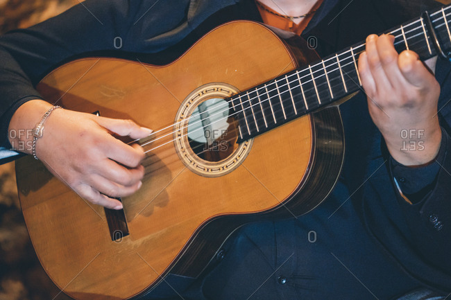 Close-up of mature man playing flamenco on guitar while performing in club