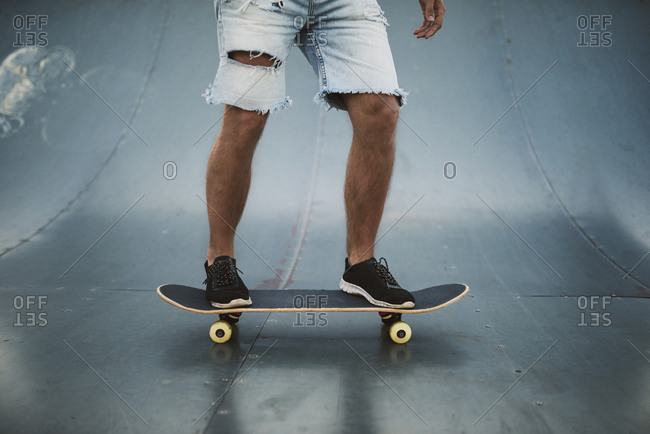Young man skateboarding on sports ramp at park