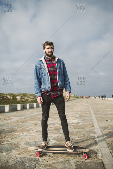 Handsome bearded man skateboarding on footpath against cloudy sky in park
