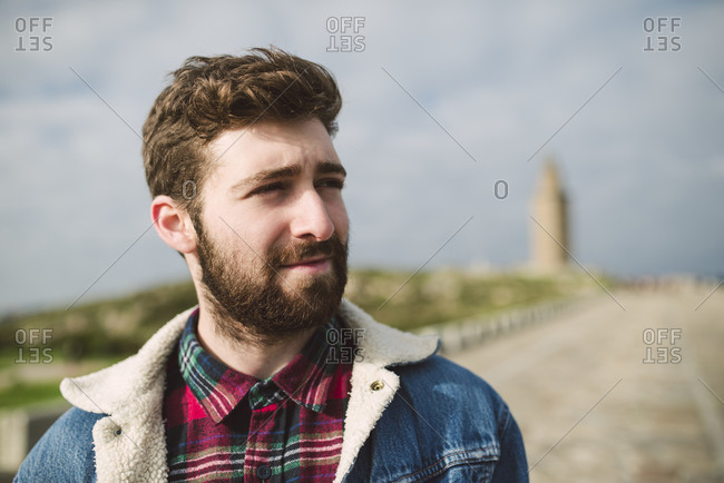 Close-up of thoughtful bearded man looking away against cloudy sky