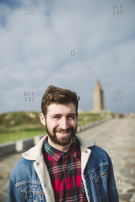 Close-up of smiling bearded man standing on footpath against cloudy sky in park