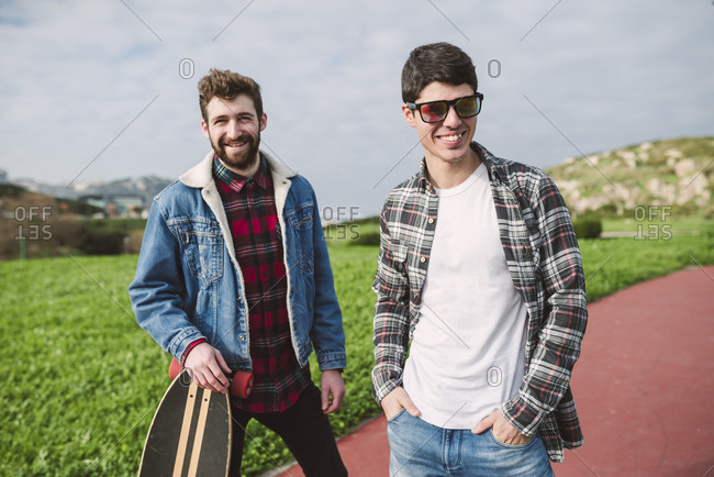 Smiling male friends standing on footpath against cloudy sky in park