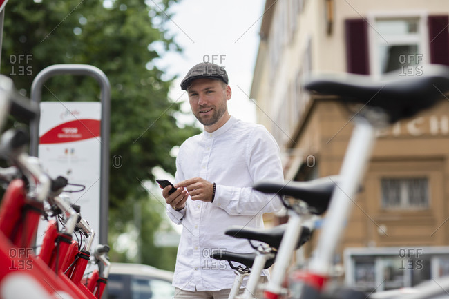 Smiling man renting bicycle through smart phone at parking station in city