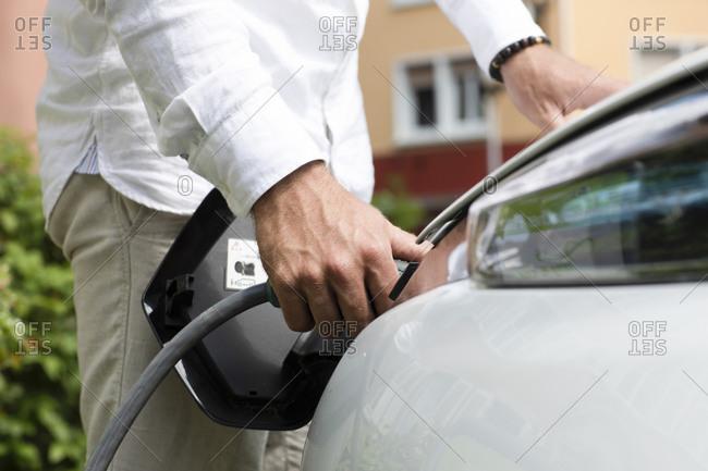 Man charging electric car at station