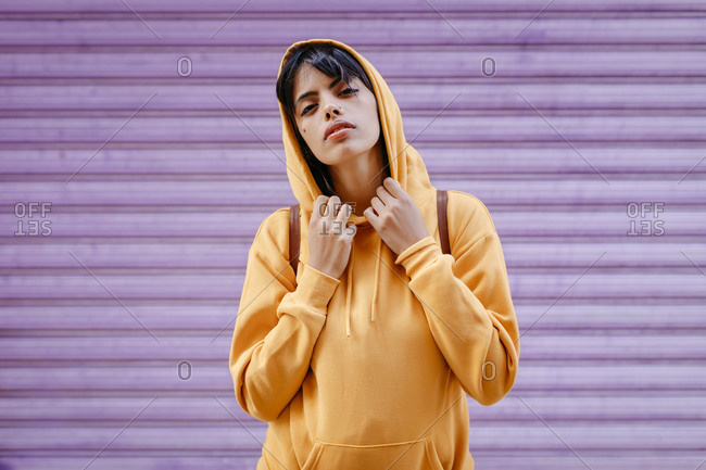 Portrait of young woman with yellow hoodie in front of purple background