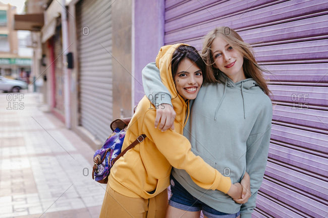 Portrait of two smiling and hugging female friends in the city