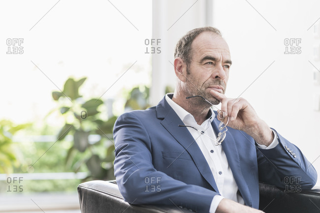 Portrait of pensive businessman sitting in armchair looking at distance
