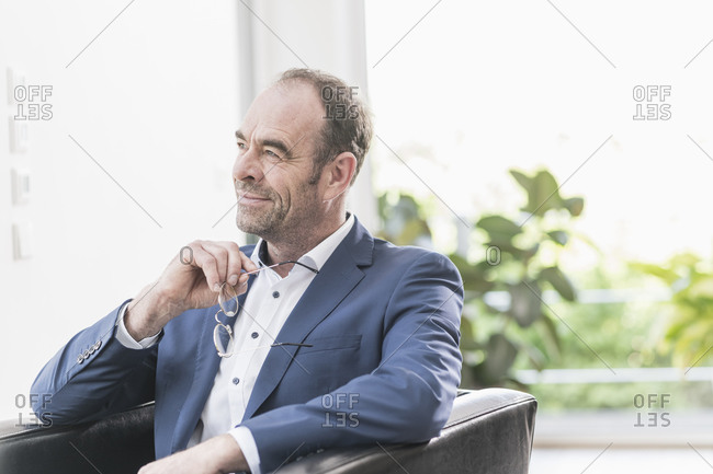 Portrait of smiling businessman sitting in armchair looking at distance