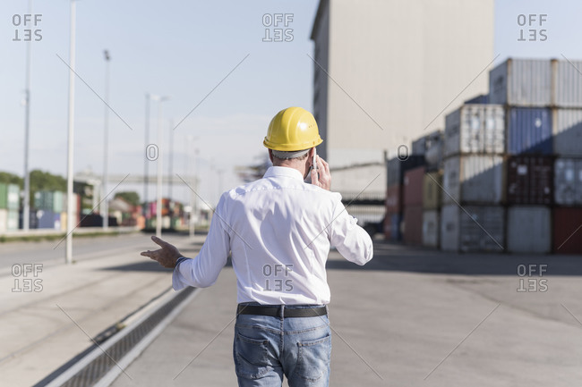 Back view of businessman on the phone wearing safety helmet at industrial site