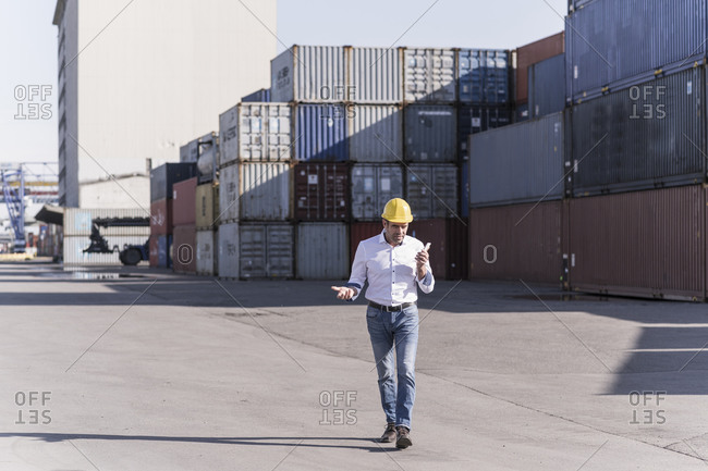 Businessman wearing safety helmet using mobile phone at industrial site