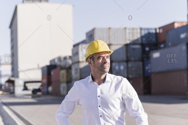 Portrait of businessman wearing safety helmet at industrial site