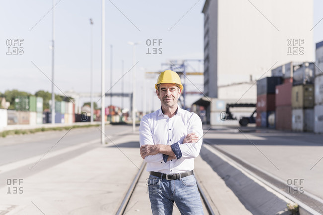 Portrait of businessman wearing safety helmet in front at industrial site