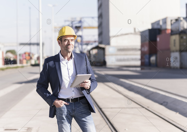 Portrait of content businessman wearing safety helmet with digital tablet at industrial site