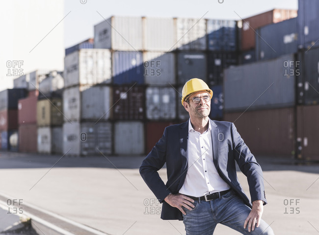 Portrait of relaxed businessman wearing safety helmet at industrial site