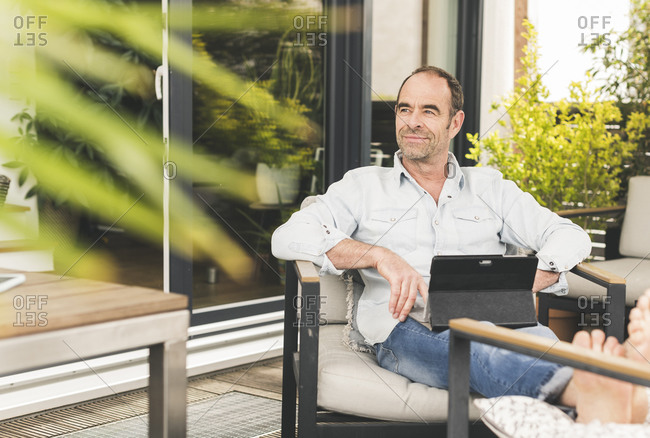 Thoughtful mature businessman looking away while sitting with digital tablet at back yard