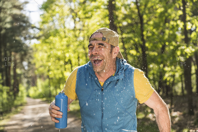 Cheerful man looking away while standing amidst water drops at park