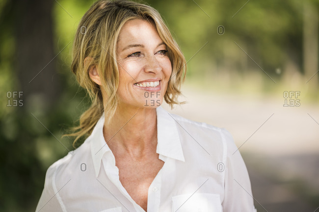 Thoughtful mature businesswoman smiling outdoors during sunny day