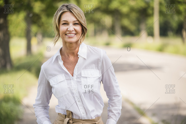 Confident mature businesswoman smiling while standing outdoors