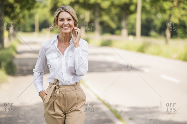 Confident mature businesswoman smiling while standing on road