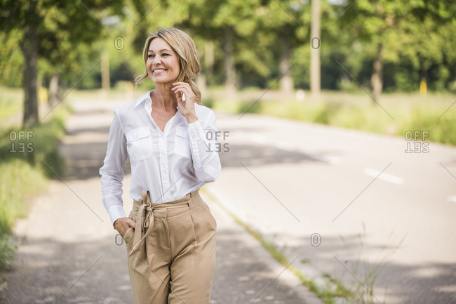 Thoughtful mature businesswoman smiling while standing on road