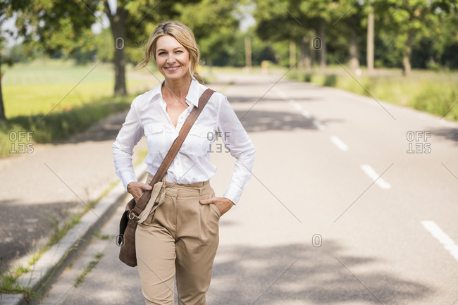 Confident mature businesswoman carrying shoulder bag while walking on road