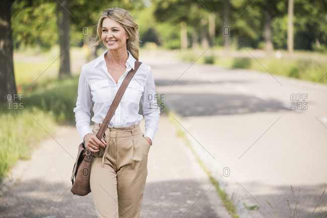 Thoughtful businesswoman carrying shoulder bag while walking on road
