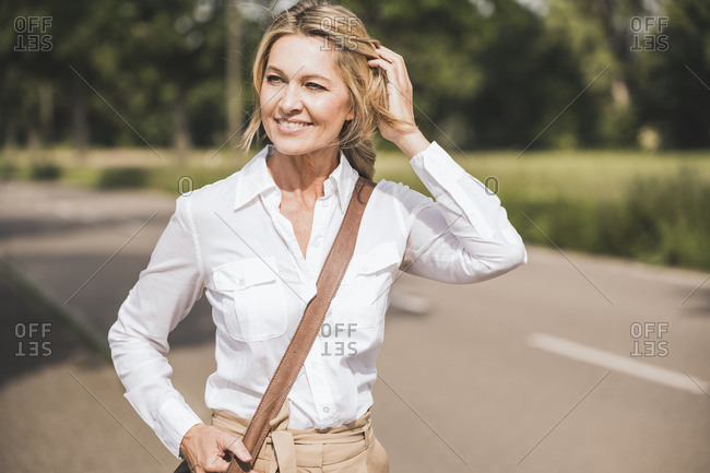 Thoughtful businesswoman carrying shoulder bag on road