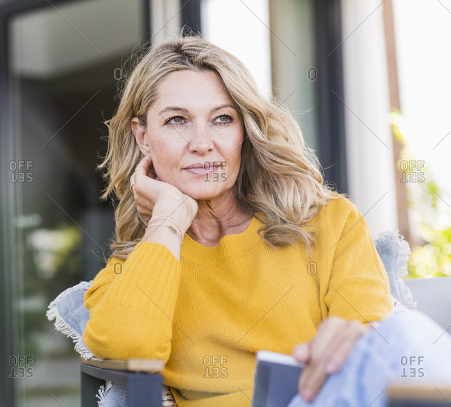 Portrait of pensive mature woman sitting on terrace with digital tablet looking at distance