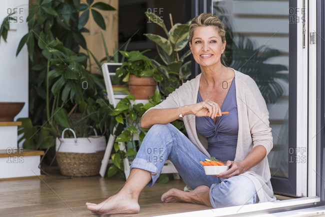 Portrait of smiling mature woman sitting on the floor at open terrace door eating finger food