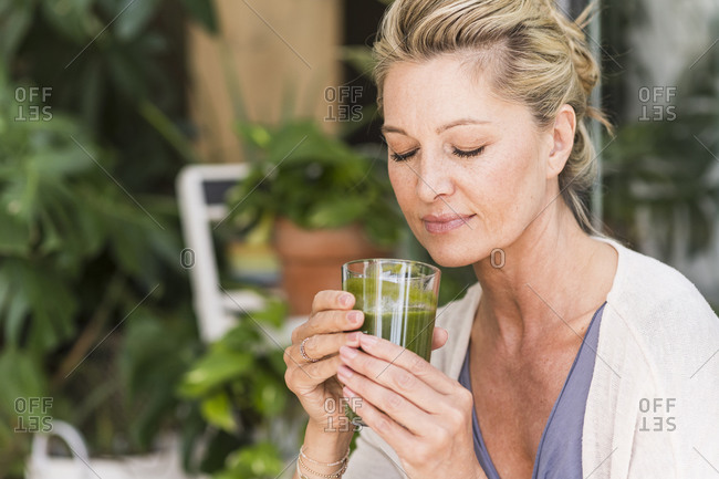 Portrait of mature woman with eyes closed with glass of green smoothie