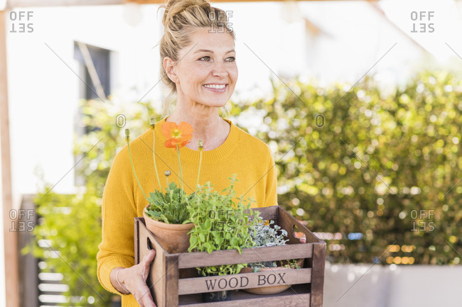 Portrait of happy mature woman with wooden box of plants on terrace