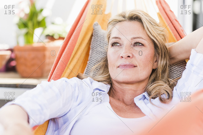 Portrait of pensive mature woman relaxing in hammock