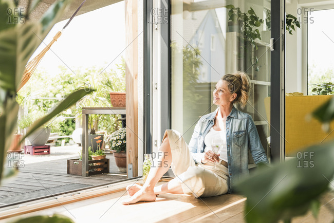 Smiling mature woman sitting on the floor at open terrace door looking at distance