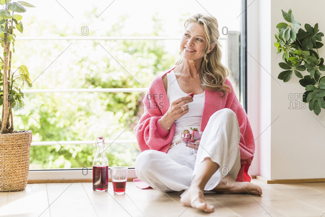 Portrait of smiling mature woman sitting on the floor at home
