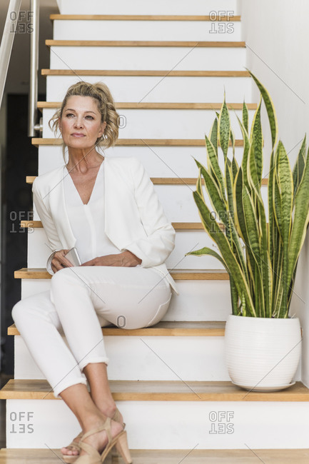 Portrait of mature businesswoman sitting on stairs looking at distance