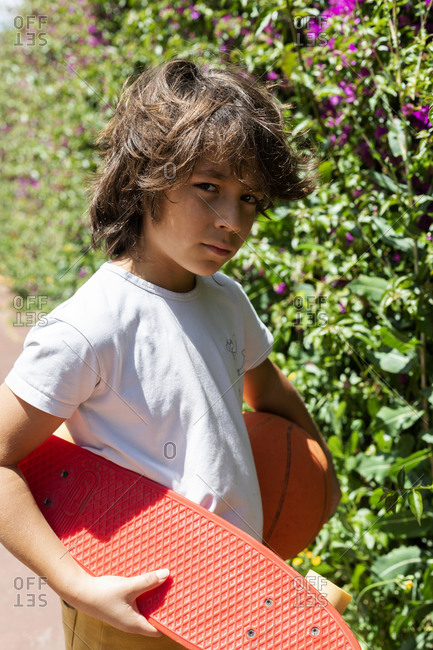 Close-up of boy with basketball and skateboard standing by plants in park