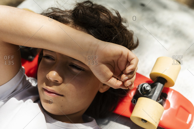 Close-up of thoughtful boy looking away while lying on skateboard