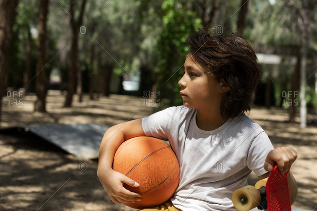 Thoughtful boy with basketball and skateboard in park