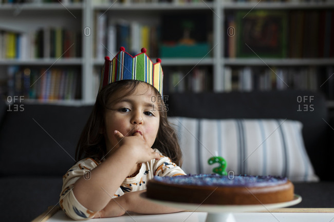 Portrait of little girl tasting birthday cake
