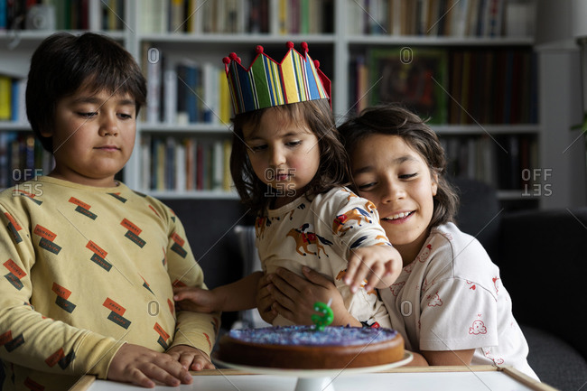 Portrait of little girl celebrating birthday with her older brothers at home