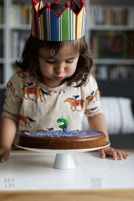 Portrait of little girl blowing out candle on her birthday cake at home