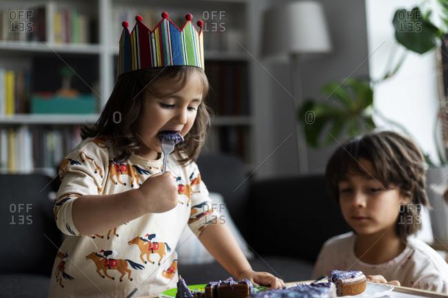 Portrait of little girl eating birthday cake