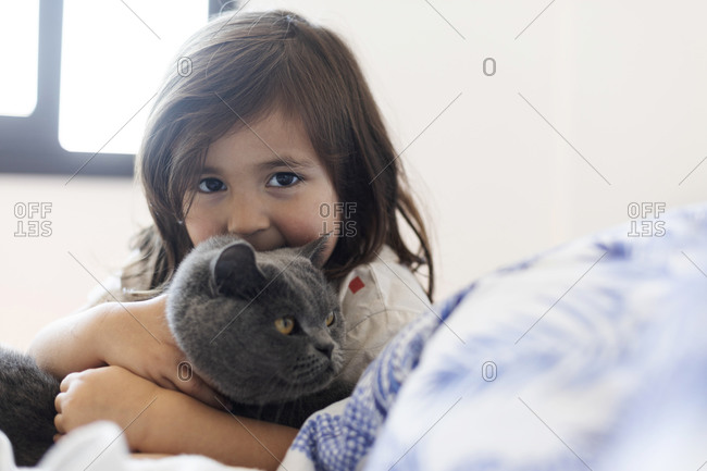 Portrait of little girl cuddling grey cat on bed
